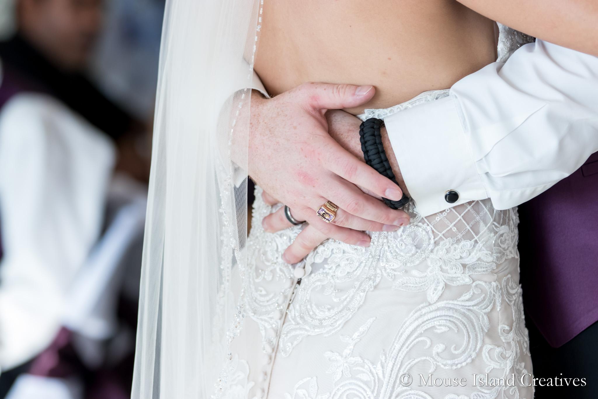 photo of groom's hands around bride's waist